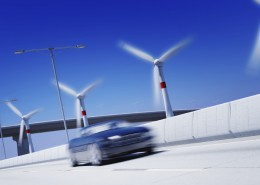 3d rendered concept of green transportation car speeding on highway with wind turbines in background(motion blur on car and turbines and Dof in background)