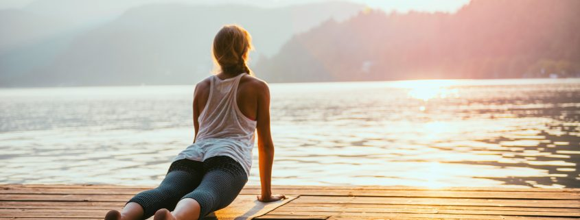 Beautiful woman practicing Yoga by the lake - Sun salutation series - Upward facing dog - Toned image