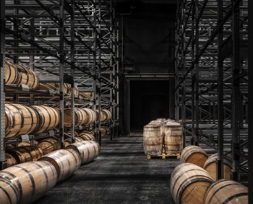 View in the most northern gin and whisky distillery in the world. Cask storage is part of the production process: Whisky must be stored in oak casks for at least three years.  The 1056 square metre black warehouse of the Finnish Kyrö Distillery is located in the middle of the forest and at first glance appears to be boarded up with old, charred wooden planks. The façade of the cask warehouse is inspired by the typical regional wooden barns.